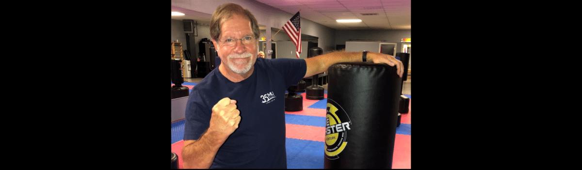 man posing next to punching bag